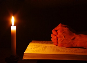 Praying-by-candle-with-bible-CONFESSION-re-sized
